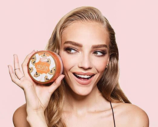 blonde girl holding coty airspun translucent powder by her face on pink background