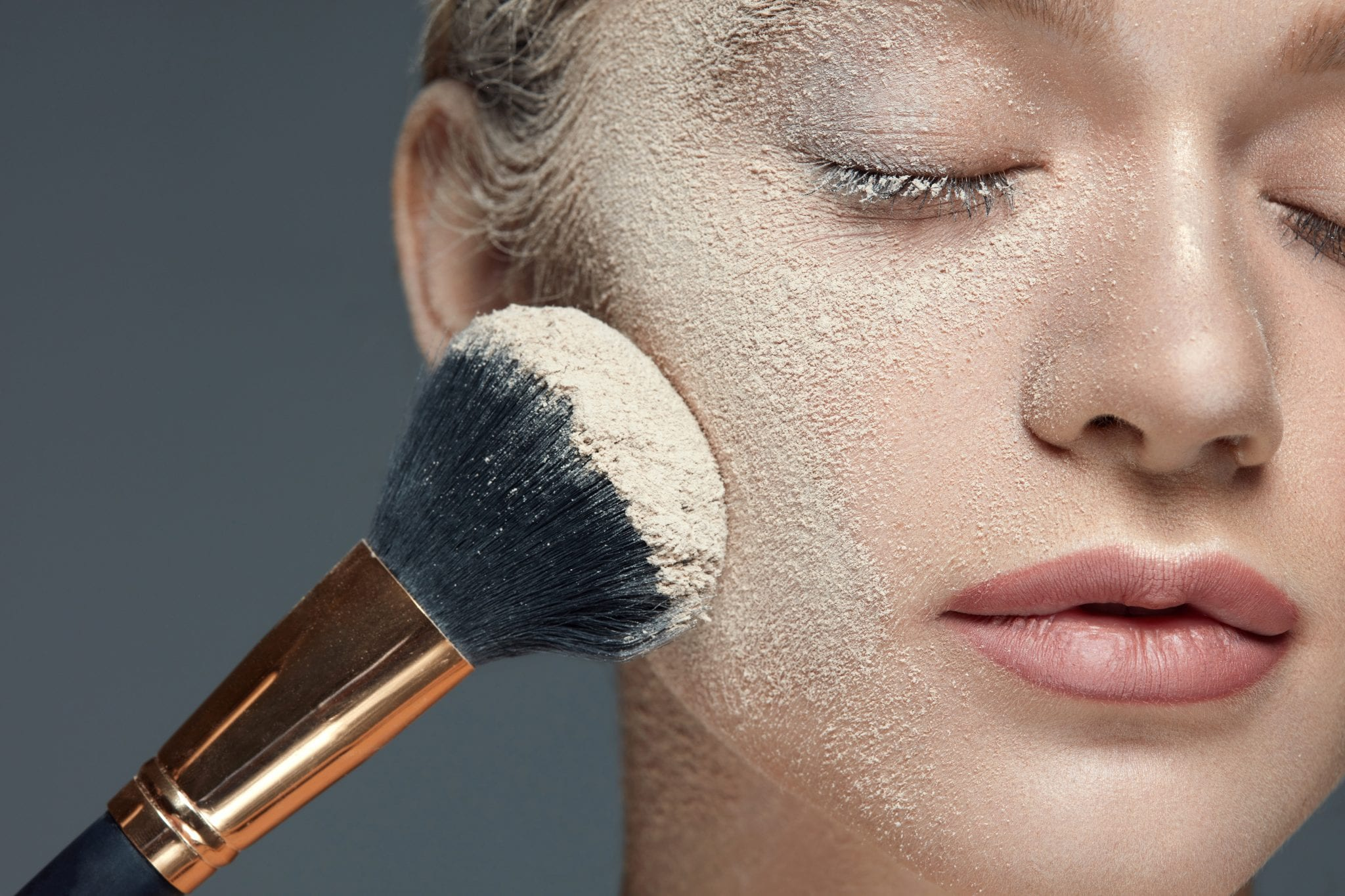 woman with eyes closed using translucent powder on her face with a fluffy brush
