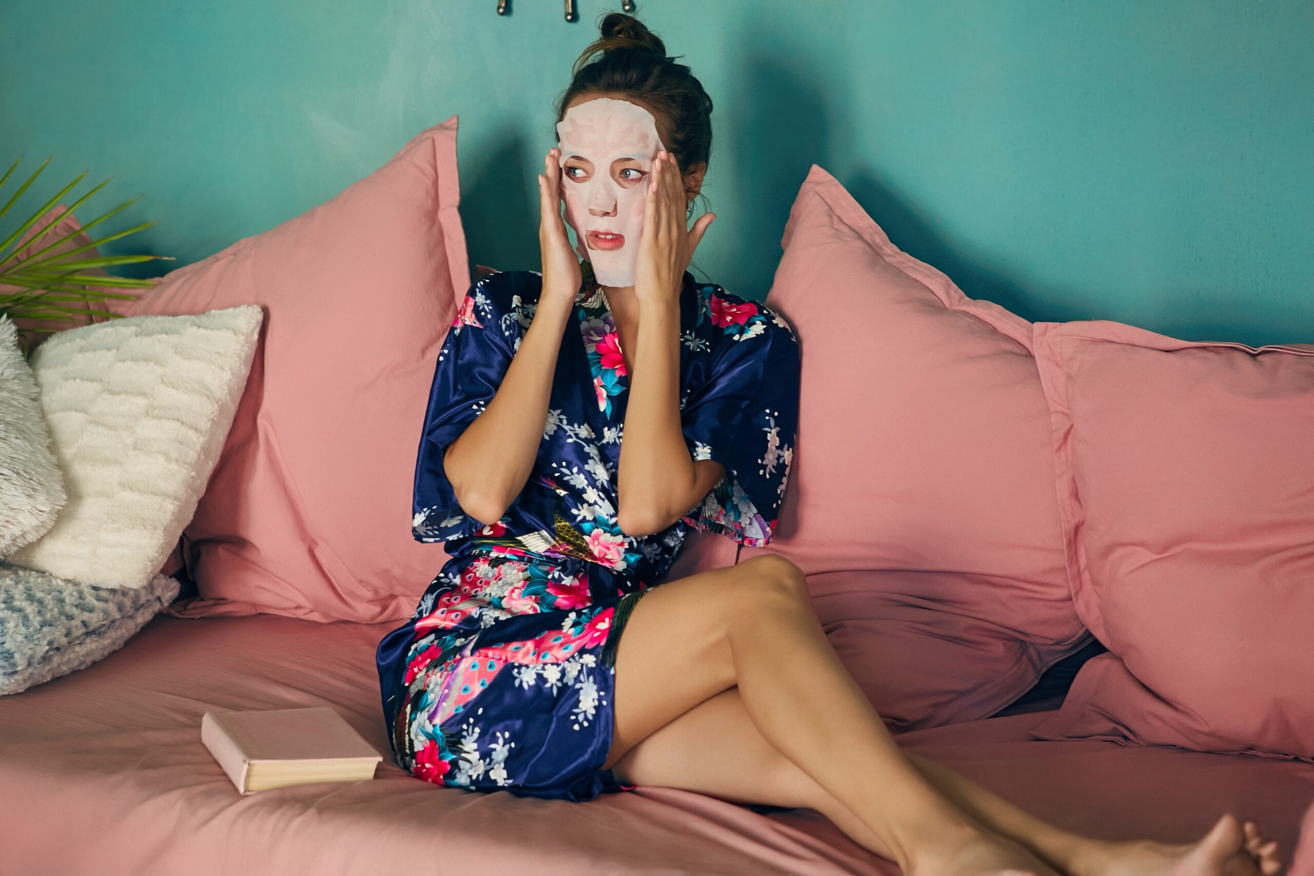 Beautiful young lady in a navy blue satin robe sitting on the pink couch enjoying her beauty procedures at home The slim brunette woman applying a white face sheet mask going to read a book