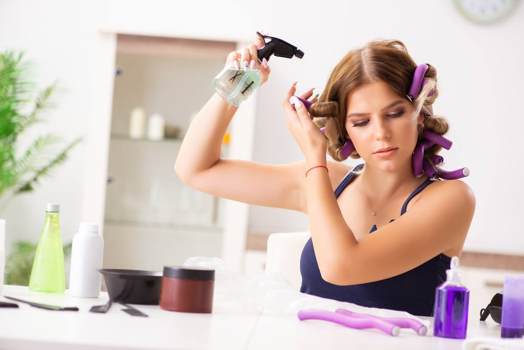young woman using curling rods and spraying with a spray bottle