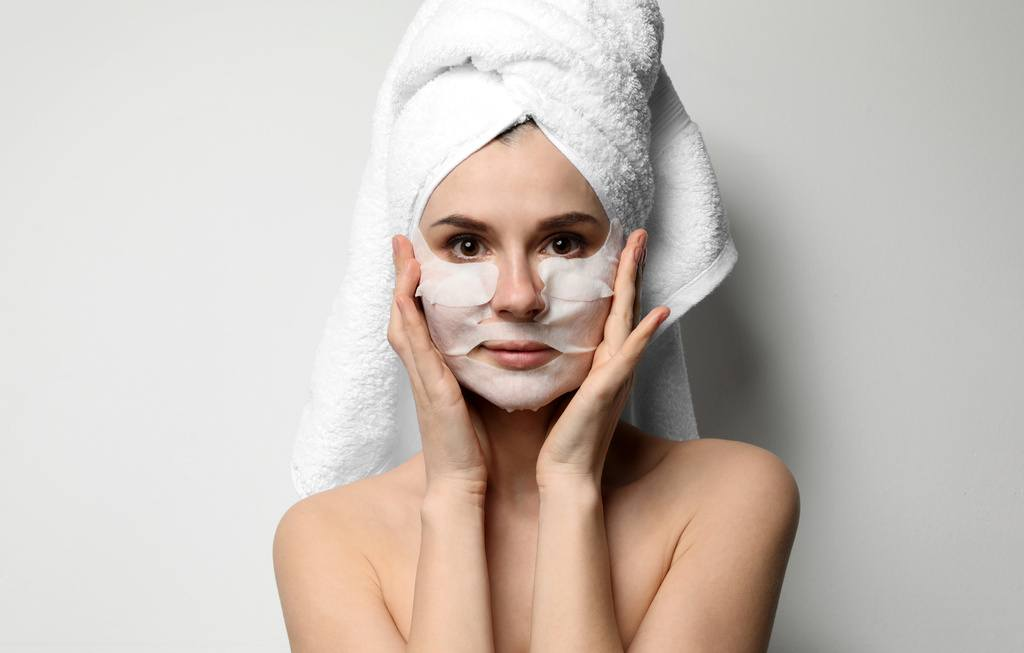 woman with hair wrapped in towel and wearing a sheet mask on bottom half of her face
