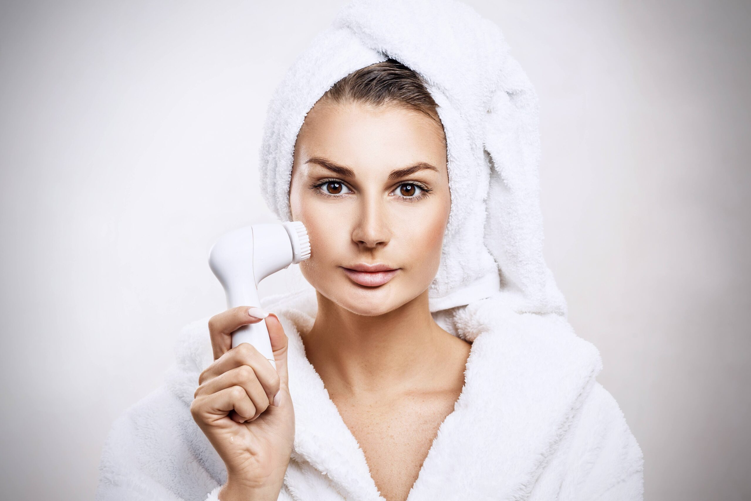 woman using a clarisonic face brush