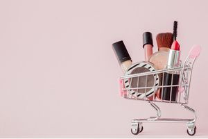 makeup products in a miniature shopping cart
