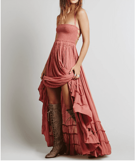 woman modeling a pink ruffled maxi dress with lace up boots
