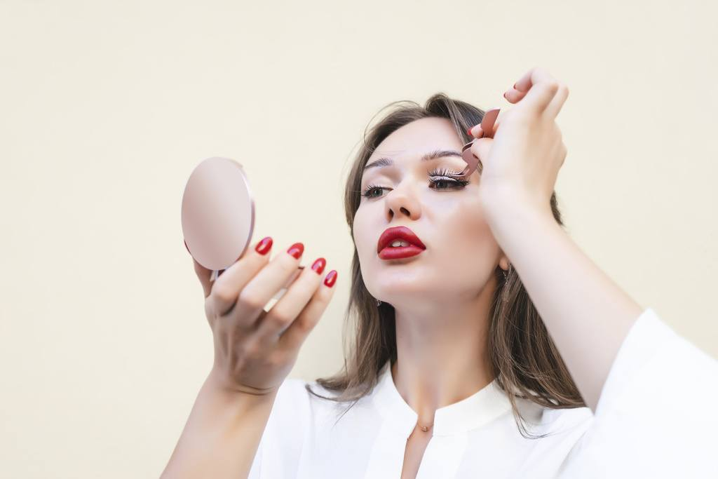 Charming woman with big red lips in white blouse applying magnetic fake eyelashes isolated on beige color.