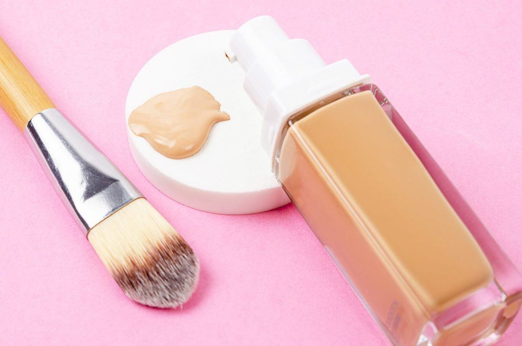 foundation pumped out on a pin background next to a makeup brush