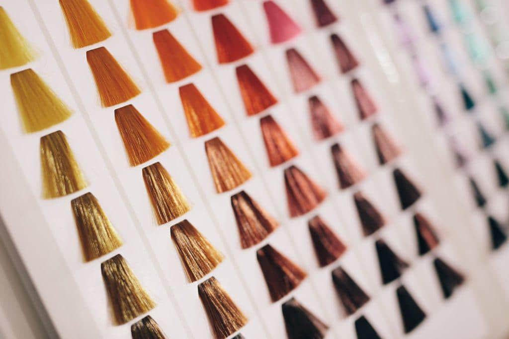 Closeup of hair samples with different color shades on a card. Hair color choice chart on display at salon.