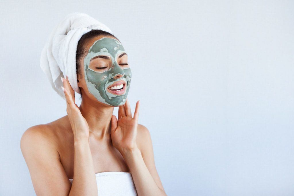woman wearing a towel on her head and wearing the Aztec Secret Indian Healing Clay Mask