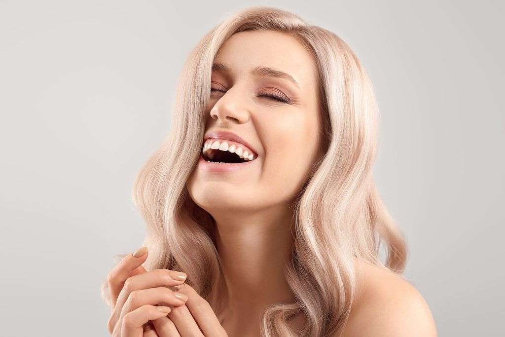 a woman laughing with gorgeous blonde hair