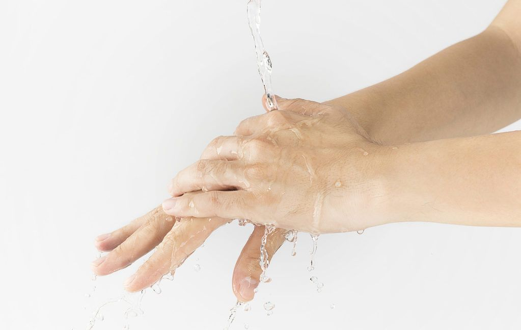 Someone rinsing their hands in a preparation for a gel manicure
