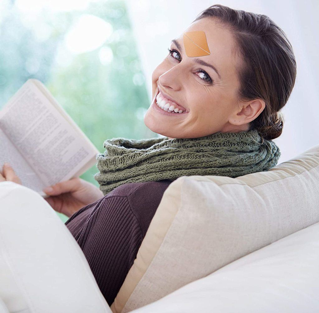 A woman smiling and reading a book while looking at the camera and sitting on a couch