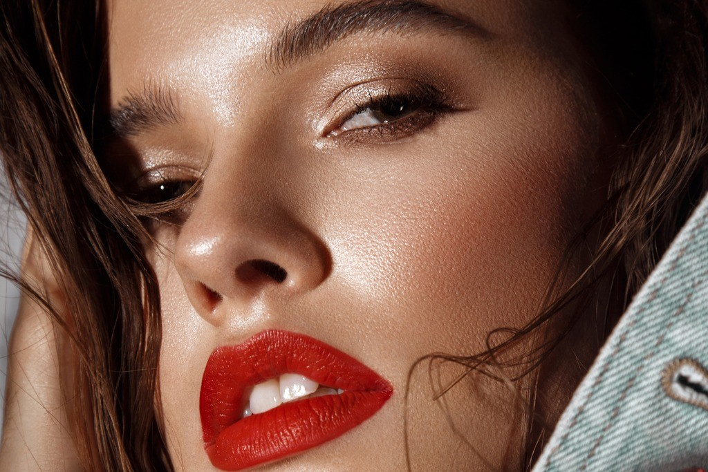 A woman with glowing skin and a bold red lip Red lips are a beauty trend in 2021