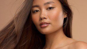 A portrait of a beautiful Asian woman on a tan background with stunning hair.