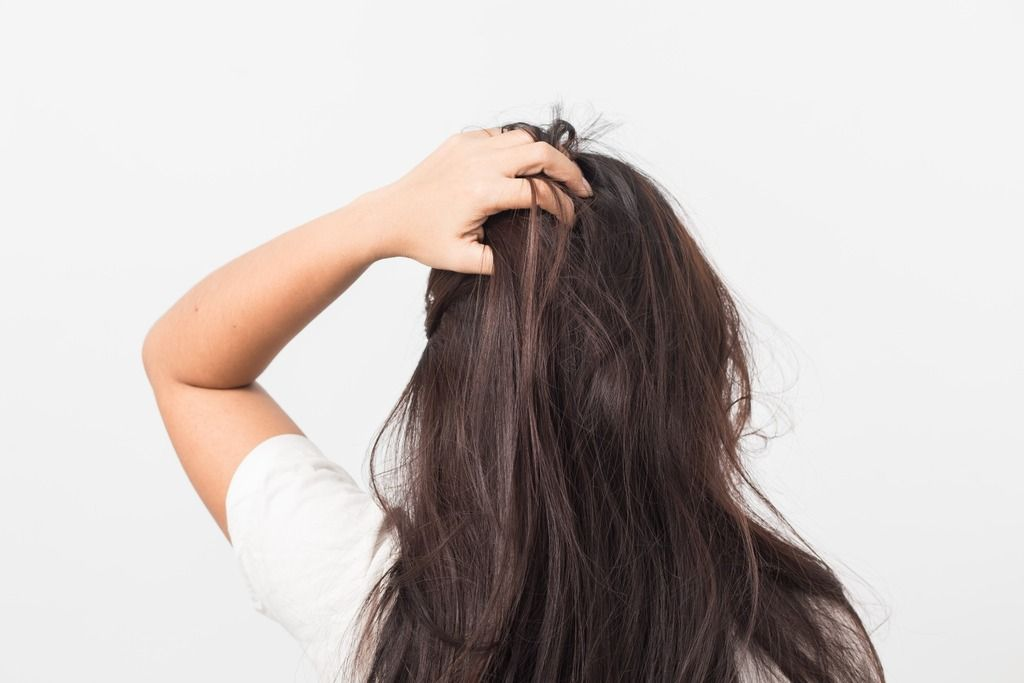 A brunette woman with an itchy scalp