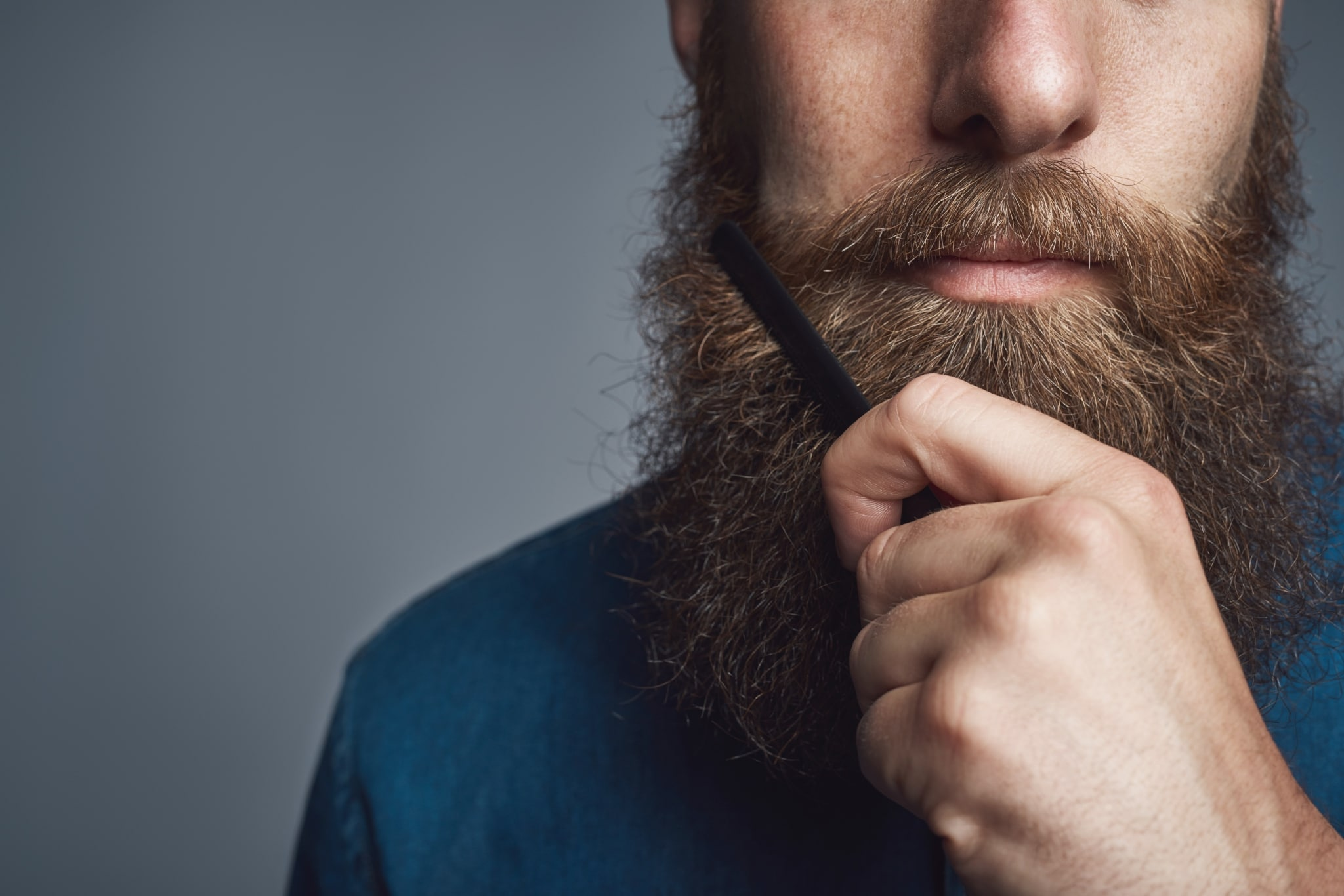 A man with a long beard using a black plastic comb to brush it